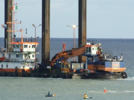 The dredger is being towed away by another vessel whilst protestor stands on digger.